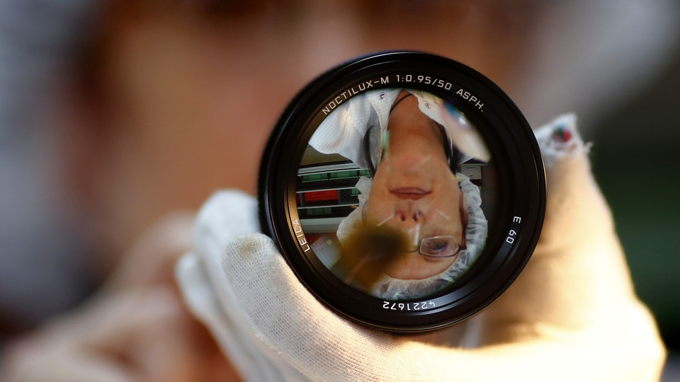 A technician is reflected in a 50-mm Leica Noctilux lens.