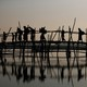 Rohingya refugees cross a bamboo bridge.