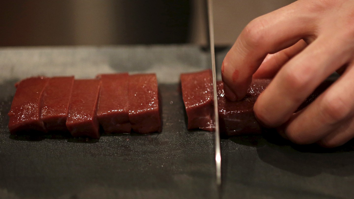 A knife chops a line or raw beef.