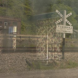 a double exposure of curtains on a railroad sign and building