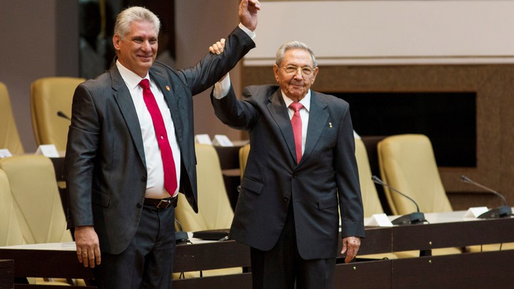 Newly elected Cuban President Miguel Diaz-Canel reacts as Raul Castro raises his hand during the National Assembly in Havana on April 19, 2018.