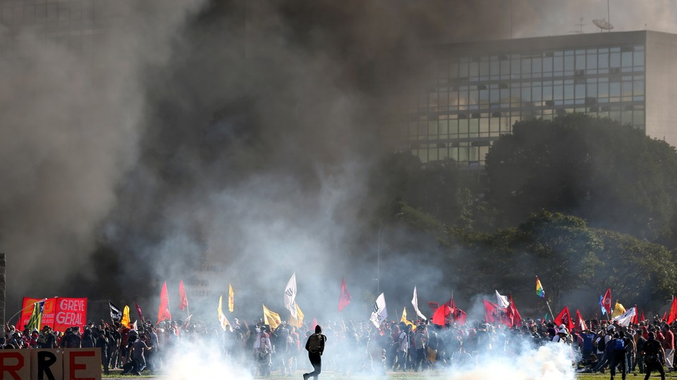 Smoke rises near Brazil'sAgriculture Ministry building during a protest against President Michel Temer and government corruption in Brasiliaon May 24, 2017.
