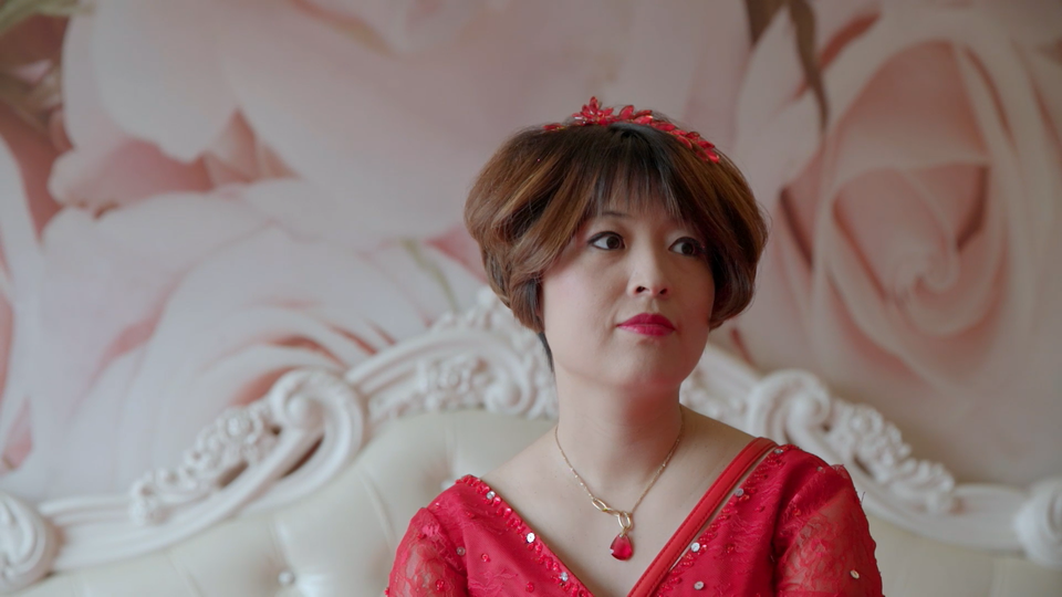Closeup of Gai Qi, one of the women in the documentary, wearing a red dress against a pink backdrop.