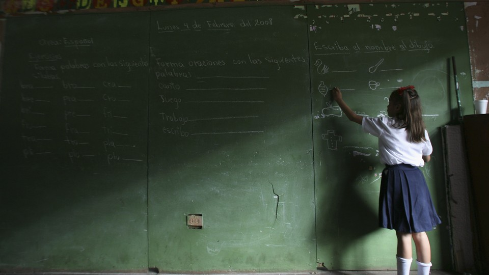 A child writes on a large chalkboard. Half the image is in shadows.