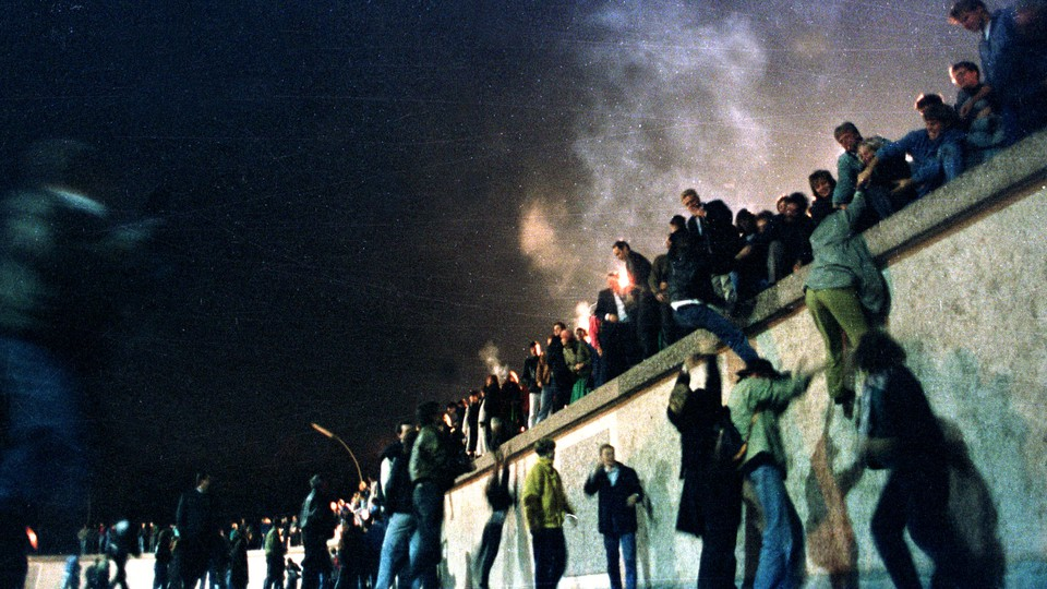 East German citizens climb over the Berlin Wall into West Berlin.
