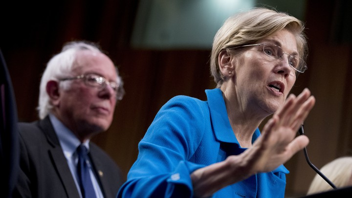 Democratic Senator Elizabeth Warren, accompanied by Senator Bernie Sanders, speaks at a health-care news conference on Capitol Hill.