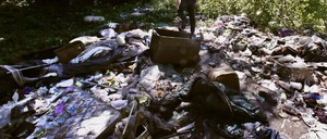 A man climbs on a garbage dump in a wooded area