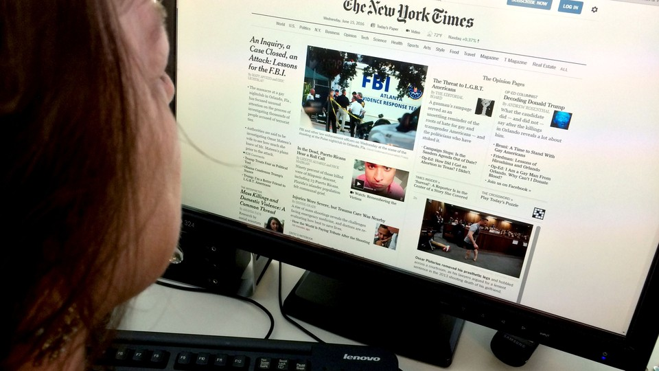 A woman reads The New York Times on her computer