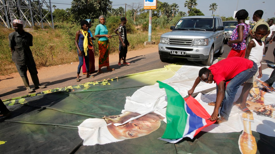Supporters of President-elect Adama Barrow lay a Gambian flag across a poster of incumbent President Yahya Jammeh.