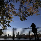 The leaves on trees frame a woman who stands at the fence around the reservoir in Central Park in New York City.