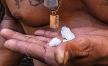 """Close-up view of 3 bright-white crystal rocks resting in a man's palm in front of his bare tattooed chest and necklaces, one with a rectangular pendant with the word """"POWER"""""""