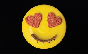 photo of yellow frisbee with 2 heart-shaped ground-beef patties as eyes and arc of dog collar as smile
