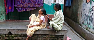 A woman combs her mother's hair outside their home in a Kolkata slum.