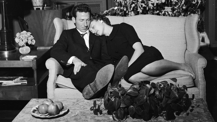 A couple relax on the couch, in black and white