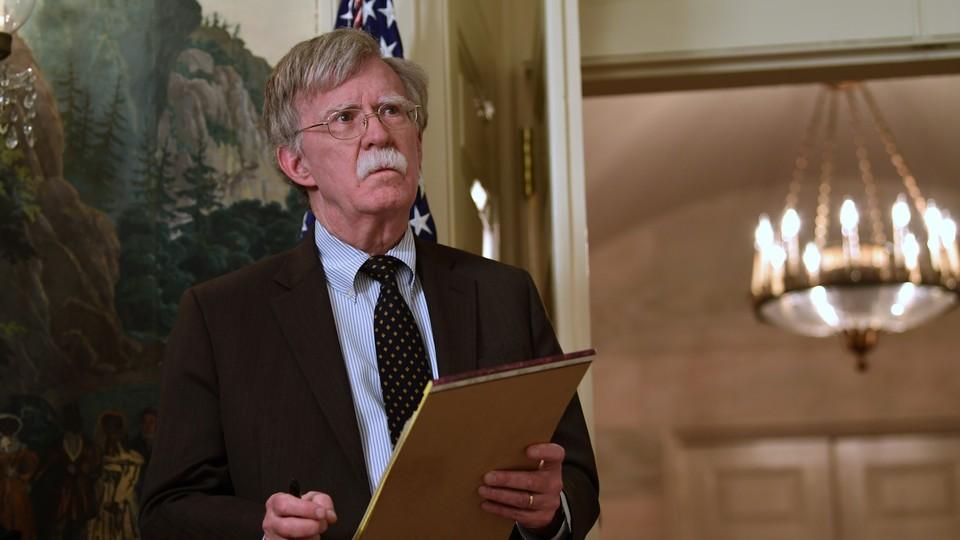 John Bolton holding a legal pad