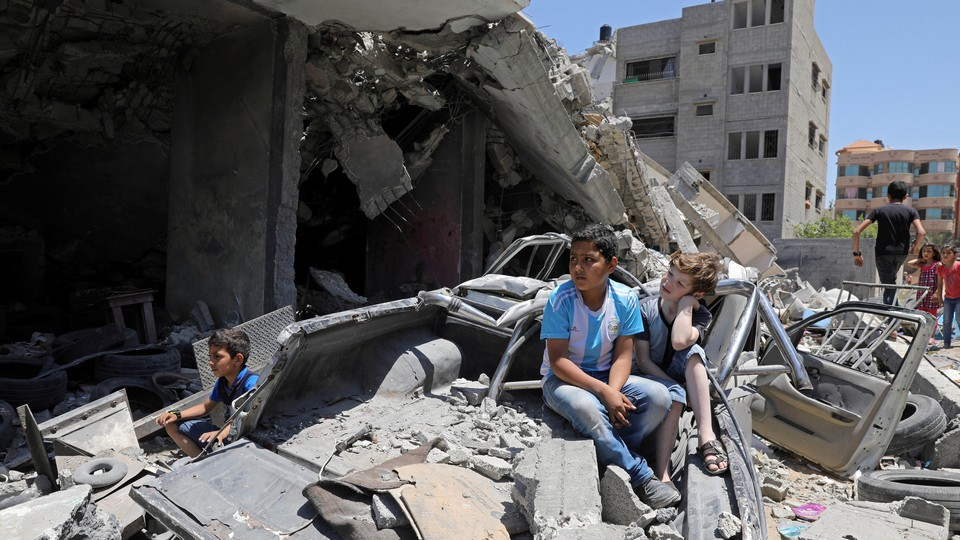 Palestinian children watch a band perform from the rubble of a building destroyed by Israeli air strikes.