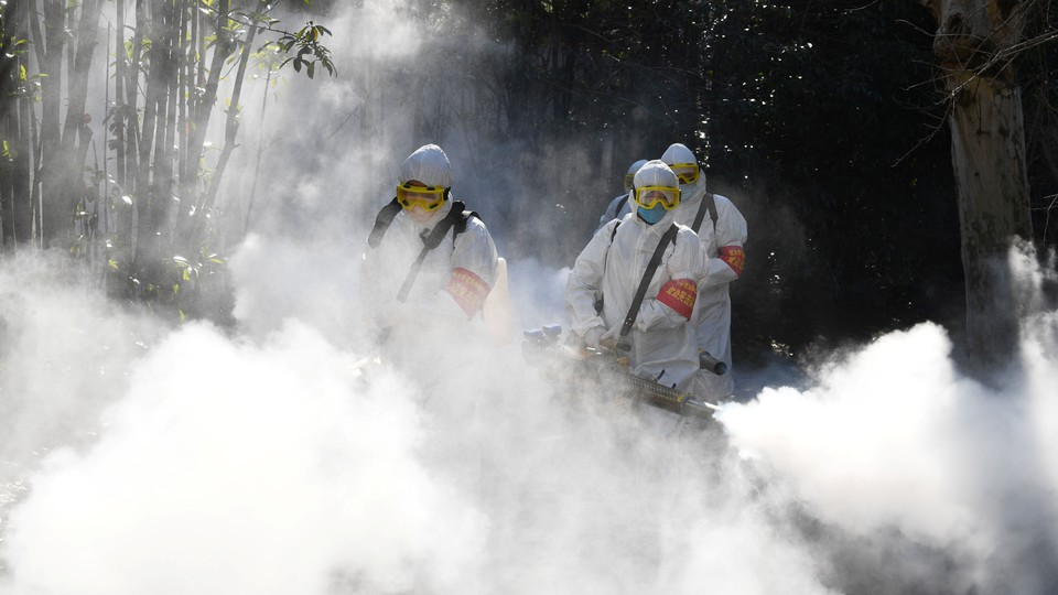 Sanitation workers disinfect a residential compound in China.
