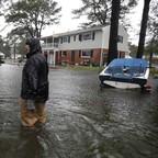 A man in a raincoat walks through knee-high water behind his house.