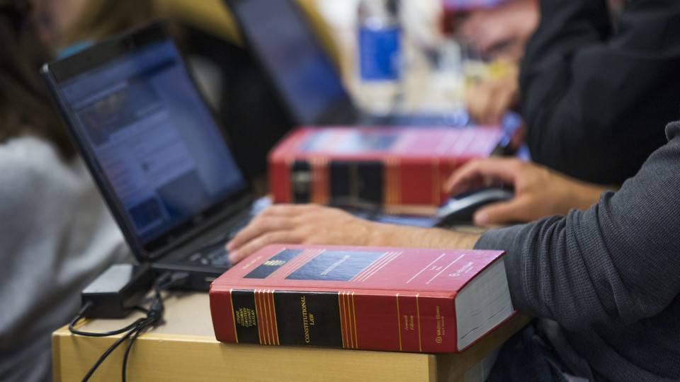 A student working on a laptop with a textbook nearby.