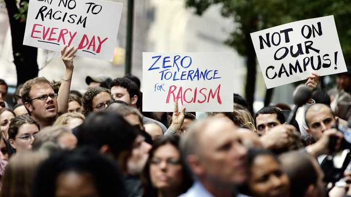 """People hold signs reading """"say no to racism every day,"""" """"zero tolerance for racism,"""" and """"not on our campus!"""""""
