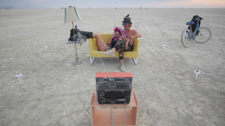Two people sitting on a yellow sofa watching TV at Burning Man