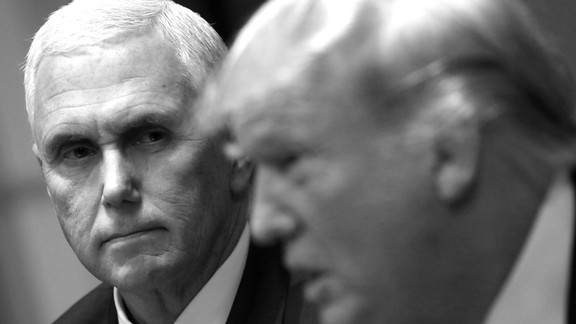 A black-and-white image shows Vice President Mike Pence looking at President Donald Trump as he speaks.