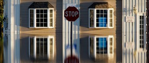 A building and street signs are reflected in flood waters.