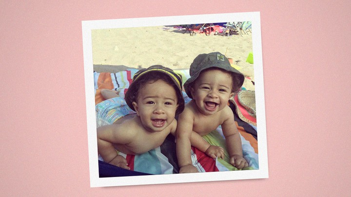 Two twin babies laying on a colorful towel at the beach