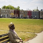 A photo of a man sitting on a bench in East Baltimore.
