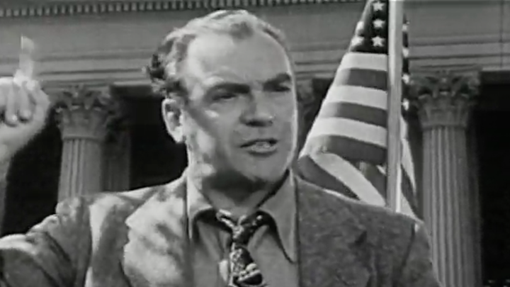 A man stands in front of an American flag with a pointed finger raised.