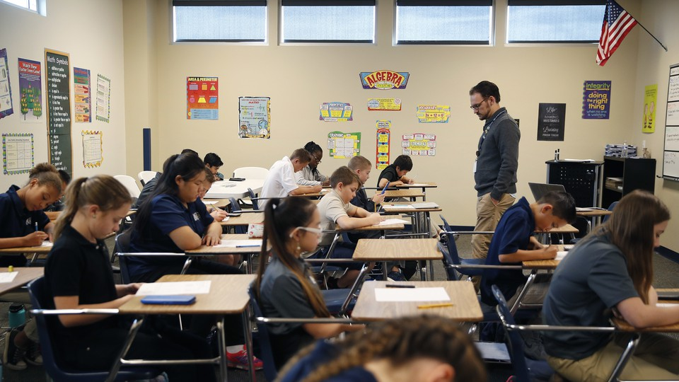 Students take a test in a classroom; a teacher stands at the front of the room.