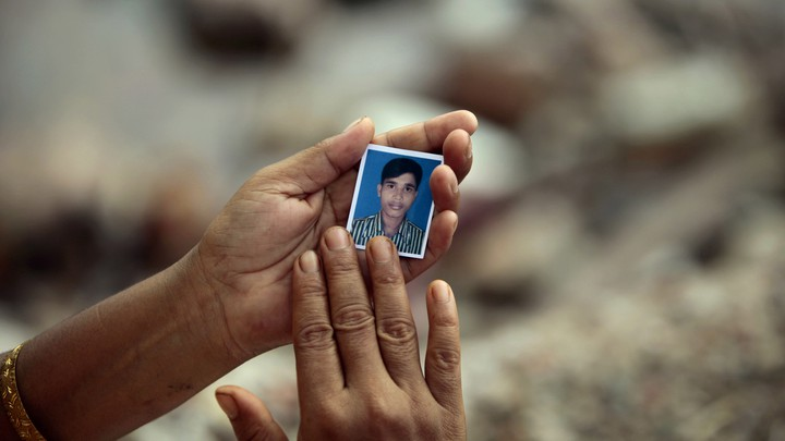 A Bangladeshi woman holds a photograph of a missing worker at the site of the Rana Plaza building collapse in 2013.