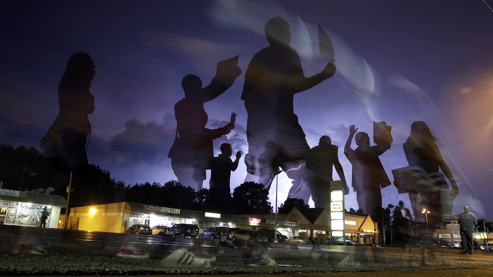 A silhouette of protestors superimposed over a strip mall