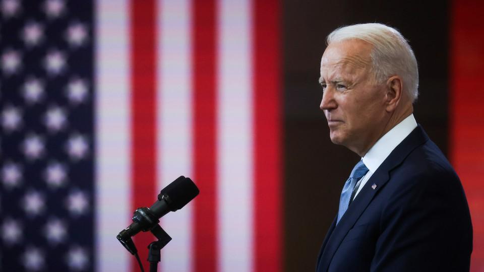 Biden speaking, flanked by American flags