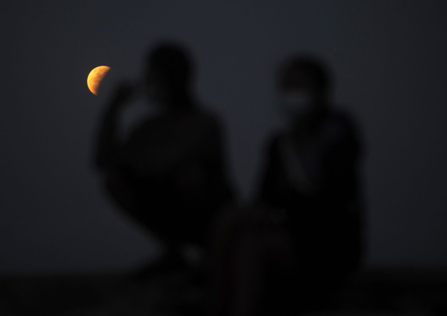 People sit on a beach, with the moon in eclipse behind them.
