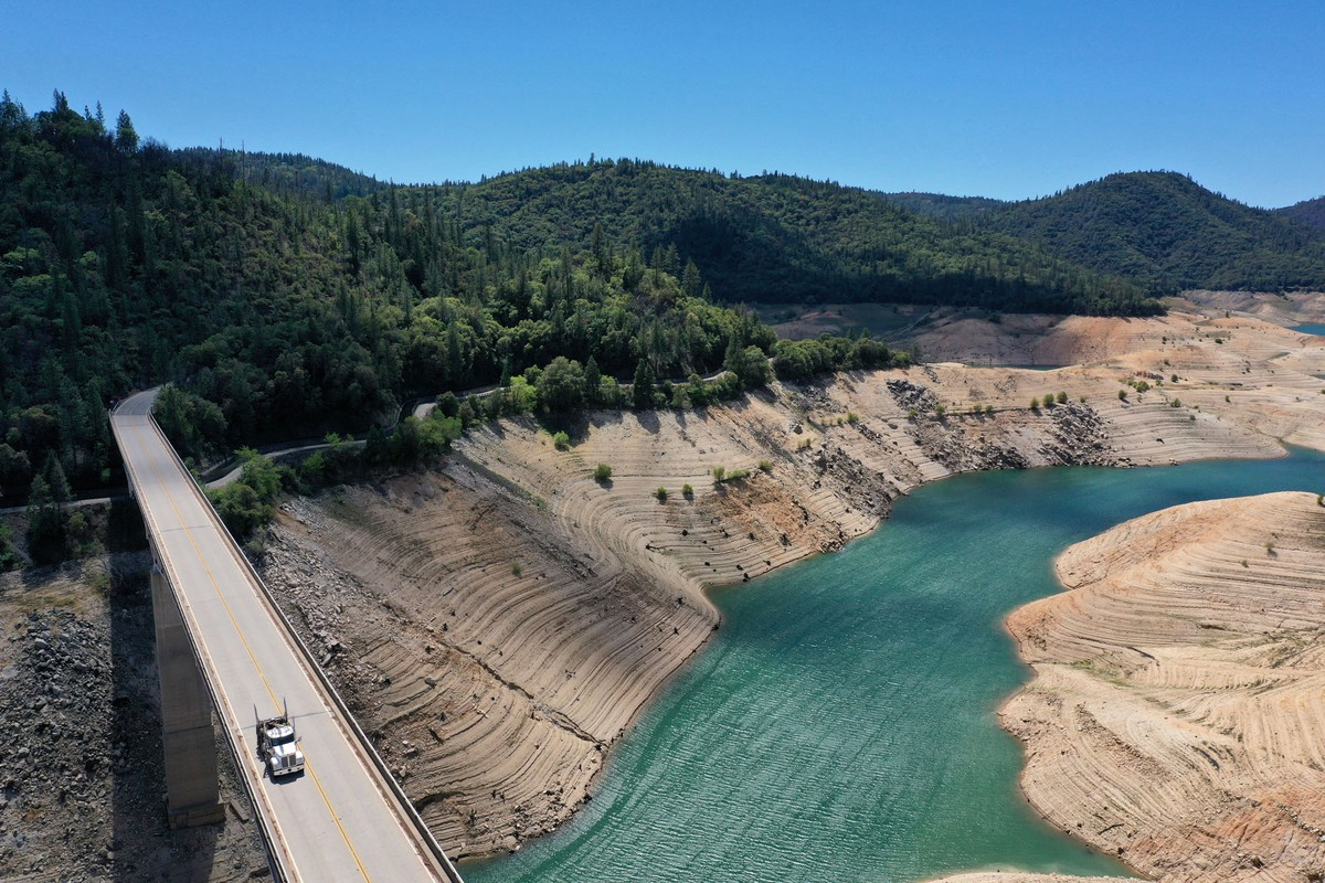 A truck drives over a bridge that spans a reservoir, which is filled with water at a very low level.
