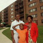 A family stands in front of their apartment building in a Chicago suburb.