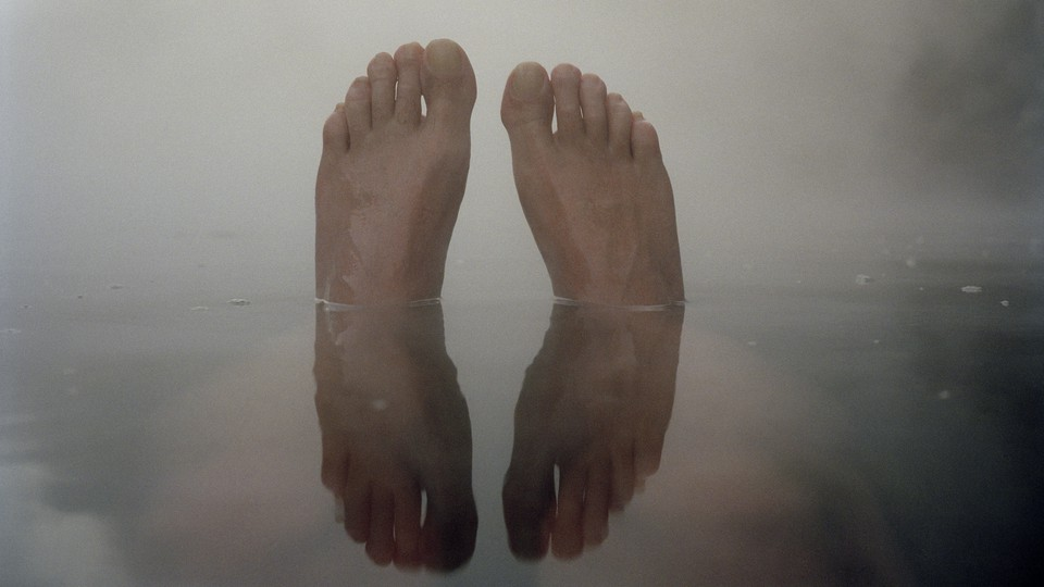A pair of feet coming out of the water, against a foggy grey sky, and reflected in the water