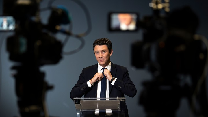 Benjamin Griveaux stands in front of video cameras while tightening his tie.