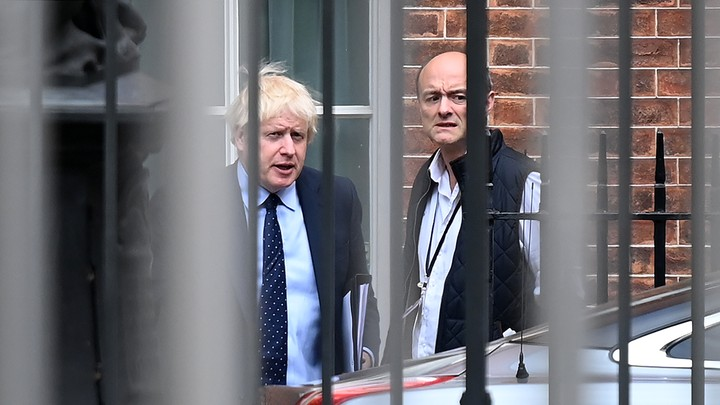 Dominic Cummings and Boris Johnson stand in the back of Downing Street behind a metal fence.