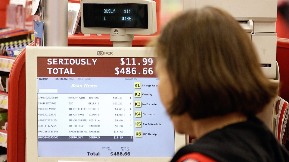 A cashier at a retail store looks at the cash register's screen.