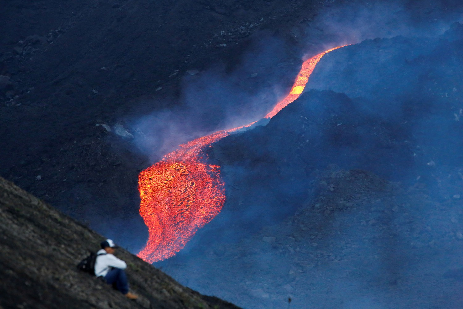 A man watches as red-hot lava flows during an eruption of the Pacaya volcano at San Vicente de Sales municipality in Guatemala's Escuintla region on May 8, 2021.