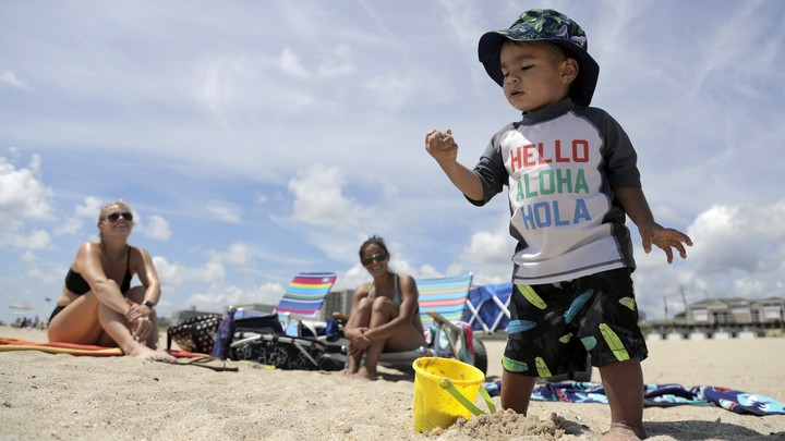 A toddler plays in the sand at the beach.