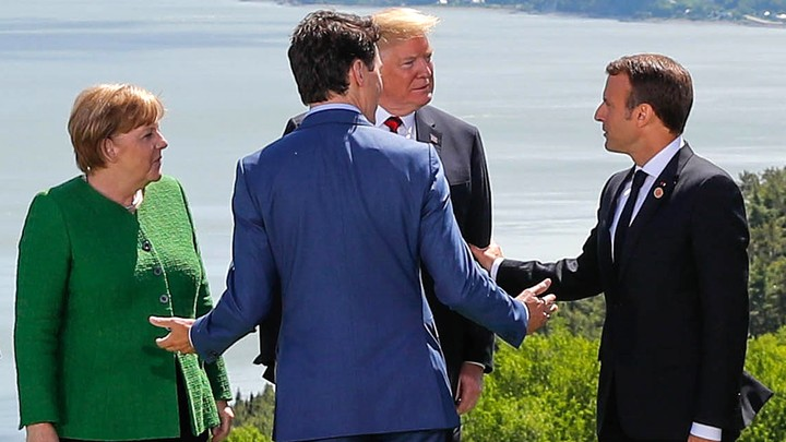 German Chancellor Angela Merkel, President Donald Trump, Canadian Prime Minister Justin Trudeau, and French President Emmanuel Macron chat at the G7 Summit in Charlevoix, Quebec on June 8, 2018.