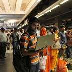 A man works on his laptop as he waits for a train at a metro station in Delhi in 2014.