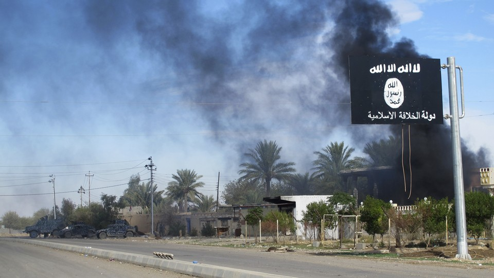 Smoke rises behind an Islamic State flag in Syria in 2014.