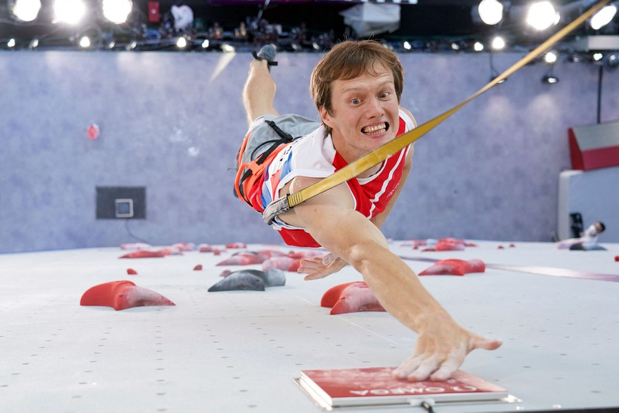 A sport climber is seen tapping a button at the top of a climbing wall.
