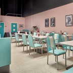 A Fifties-style diner with blue booths and chairs and pink walls.