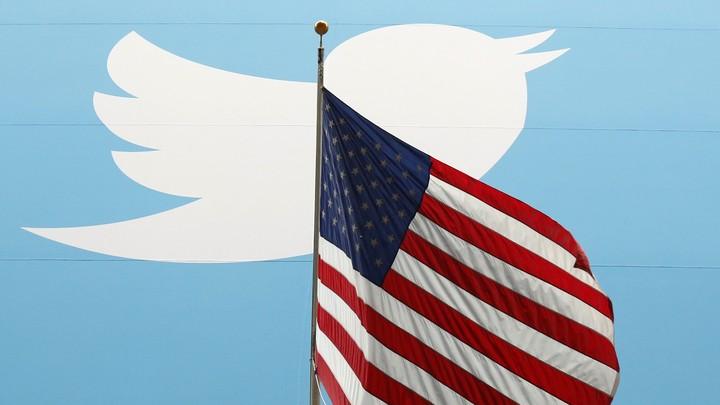 The Twitter logo behind a U.S. flag