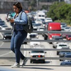 photo: A woman crosses an overpass above the 101 freeway in Los Angeles, California.